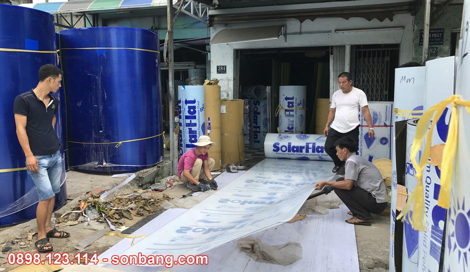 nhân viên sơn băng đang cắt tấm poly